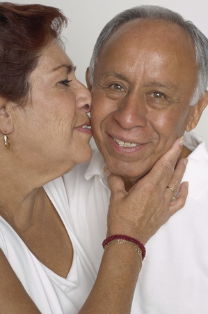 Senior Hispanic woman kissing husband