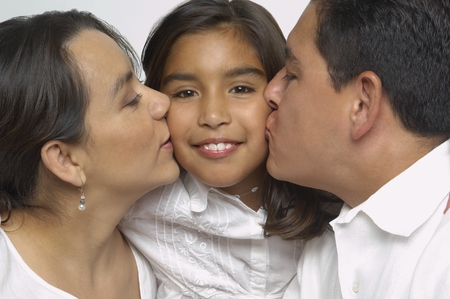 Hispanic parents kissing daughter's cheeks Stock Photo
