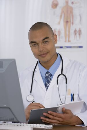 doctor writing: Male doctor writing in notebook