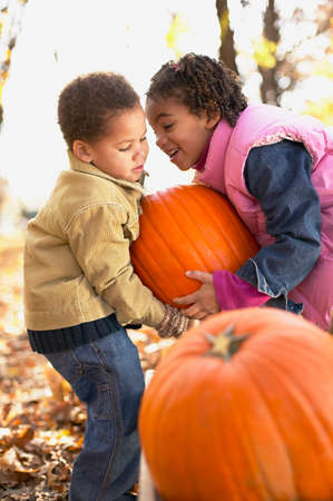 tugging: African brother and sister lifting pumpkin LANG_EVOIMAGES