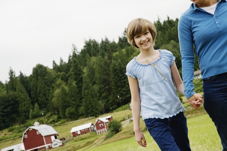 Mother and daughter holding hands on farm Stock Photo
