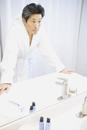 Asian man looking in bathroom mirror Stock Photo