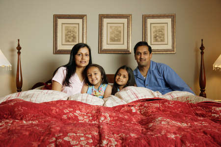 Indian family sitting in bed