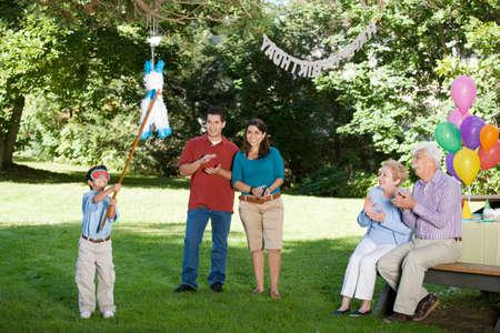 mischeif: Family watching Hispanic boy hitting pinata at birthday party