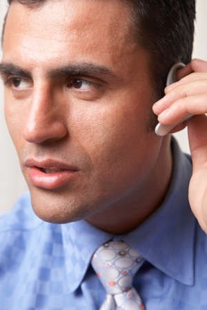 hands free device: Hispanic businessman wearing hands free device LANG_EVOIMAGES
