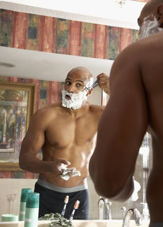 acknowledging: Mixed Race man shaving in bathroom LANG_EVOIMAGES