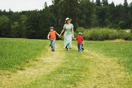 Mother and sons walking in field