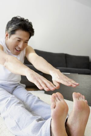 bedcover: Asian man trying to touch toes