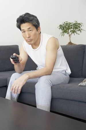 Asian man pointing remote control