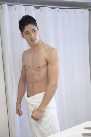 gazing: Asian man flexing in bathroom mirror LANG_EVOIMAGES
