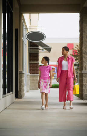 wooing: African mother and daughter window shopping LANG_EVOIMAGES