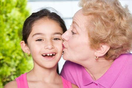 endangering: Hispanic grandmother kissing granddaughter on cheek
