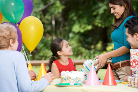 family: Hispanic girl receiving gift at birthday party in park