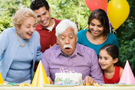 grampa: Senior Hispanic man blowing out birthday candles with family in park LANG_EVOIMAGES