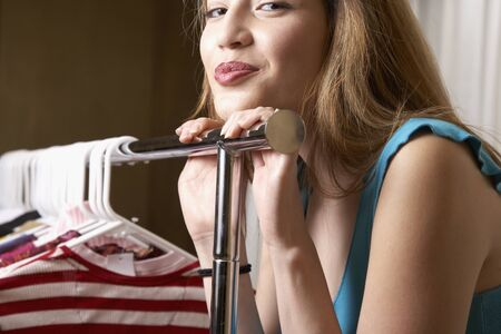 mischeif: Hispanic woman leaning on rack of clothing LANG_EVOIMAGES