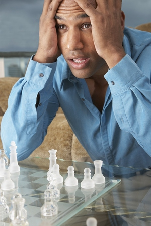 seriousness skill: Mixed Race man playing chess LANG_EVOIMAGES