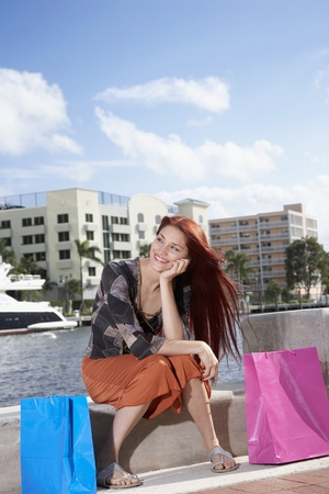 Hispanic woman sitting with shopping bags Stock Photo