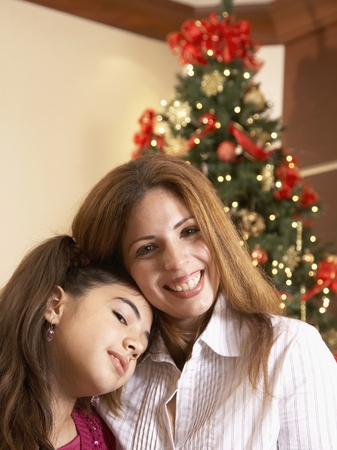 indignant: Hispanic mother and daughter in front of Christmas tree