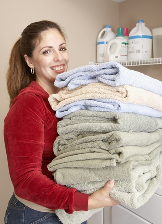 fathering: Hispanic woman carrying folded towels LANG_EVOIMAGES