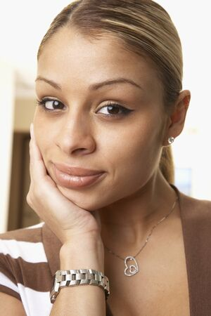 Hispanic woman resting chin in hand