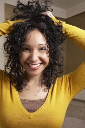 playing on divan: Hispanic woman playing with hair