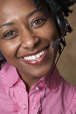 eagerness: African businesswoman wearing headset LANG_EVOIMAGES