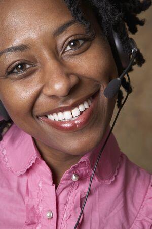 relishing: African businesswoman wearing headset LANG_EVOIMAGES