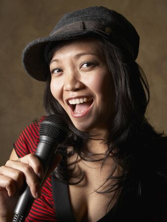 low spirited: Asian woman singing with microphone