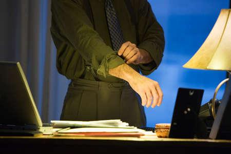 rolling up: Hispanic businessman rolling up sleeve