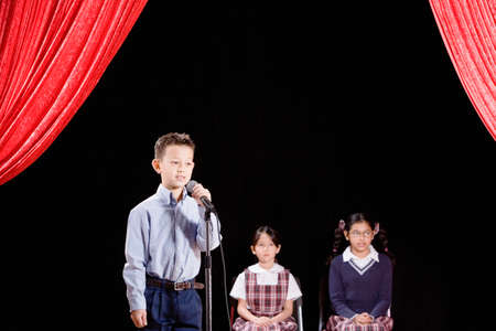 Asian boy speaking into microphone on stage Stock Photo