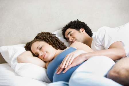 talker: Pregnant African couple sleeping in bed LANG_EVOIMAGES