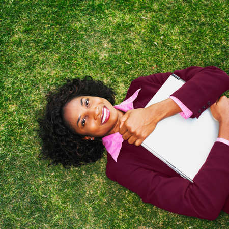 late twenties: African businesswoman laying in grass LANG_EVOIMAGES