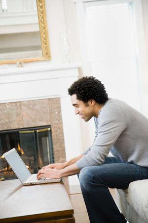 relishing: African man typing on laptop