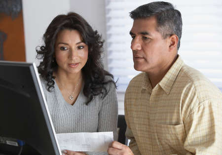 early fifties: Hispanic couple looking at computer