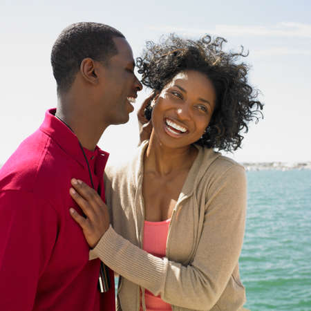 mischievious: African couple hugging at beach