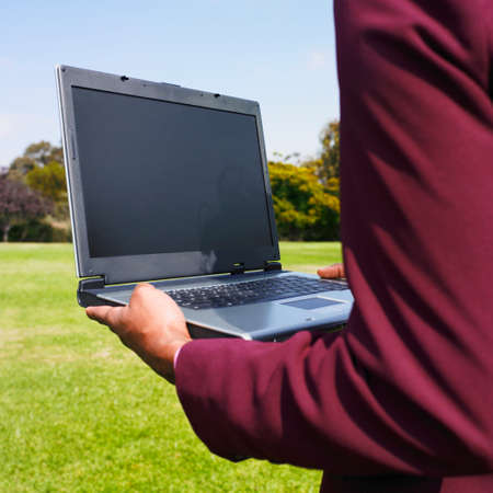 3 persons only: African businesswoman holding laptop in field