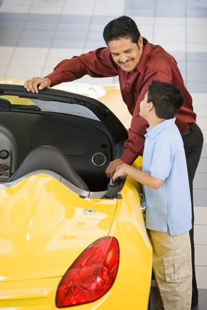 Hispanic father and son looking at new car