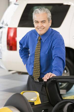western script: Hispanic car salesman leaning on new car
