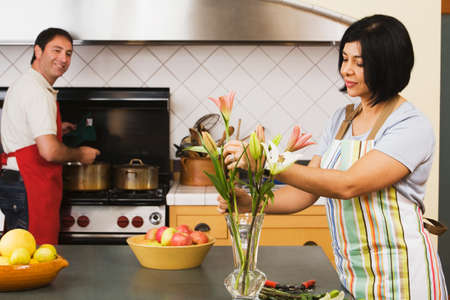 jeopardizing: Multi-ethnic middle-aged couple in kitchen LANG_EVOIMAGES