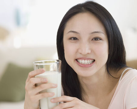 woman drinking milk: Asian woman drinking milk LANG_EVOIMAGES