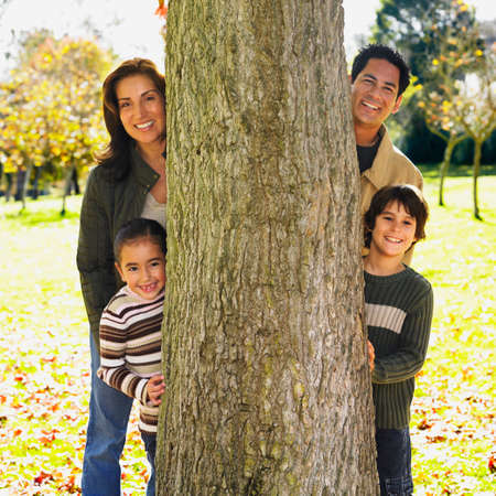 fathering: Hispanic family behind tree in park
