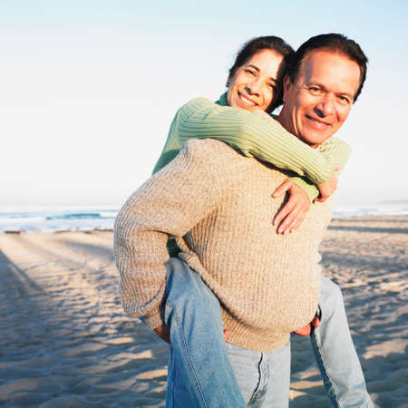 Hispanic man giving wife piggyback ride at beach Stock Photo