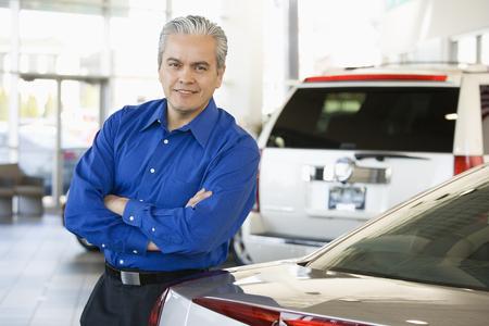 Hispanic car salesman leaning on new car Imagens - 35680219