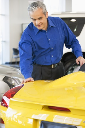 ostentatious: Hispanic car salesman looking at new car