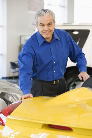 tugging: Hispanic car salesman looking at new car