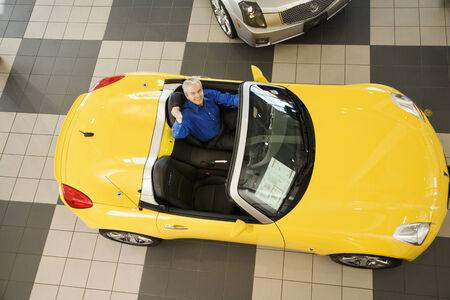 babyboomer: Hispanic car salesman sitting in new car