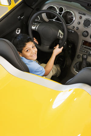 Hispanic boy sitting in new car
