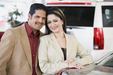 Hispanic couple at car dealership