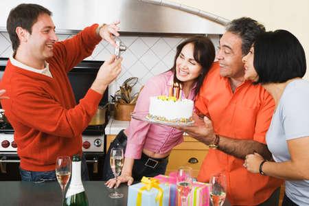 babyboomer: Middle-aged man having photograph taken on birthday LANG_EVOIMAGES