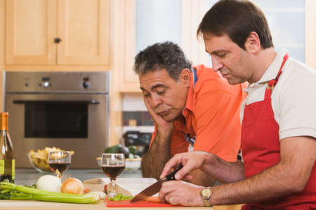 middleaged: Two middle-aged men cooking LANG_EVOIMAGES